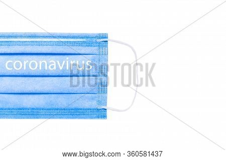 Blue Medical Mask Located On The Left Isolated On A White Background. On The Mask Is The Inscription
