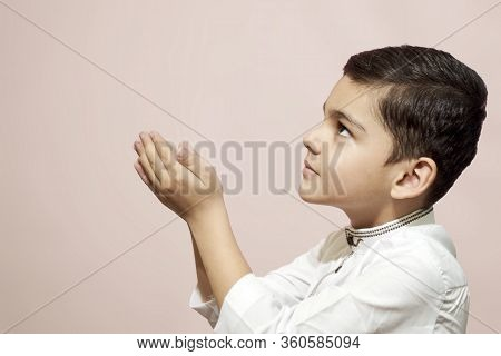 Muslim Child Praying In The Mosque. Little Middle-eastern Boy Prays To God And Thanks. Peace And Lov
