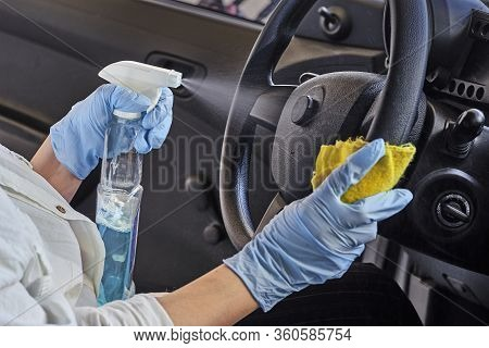 Woman In Rubber Protective Glove Disinfecting Car Steering Wheel. Cleaning Vehicle Inside For Protec