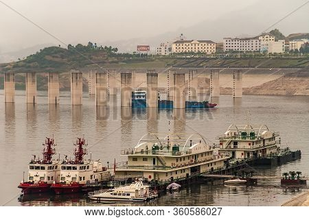 Three Gorges Dam, China - May 6, 2010: Yangtze River. Foggy Morning Closeup Of Tugboats And Office P