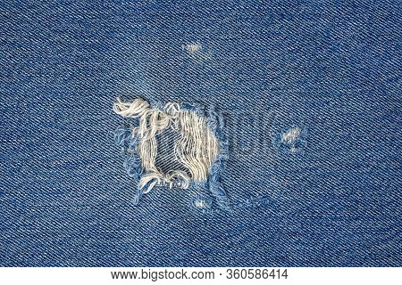 Close Up Of Frayed Hole In Blue Denim Fabric