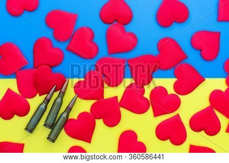 Gun Cartridges And Red Hearts On Colorful Blue Yellow Background Flat Lay Close Up. War And Peace Co