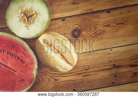 Sweet Organic Summer Muskmelons And Watermelon On The Wooden Background. Ripe Melons On Wood. View F