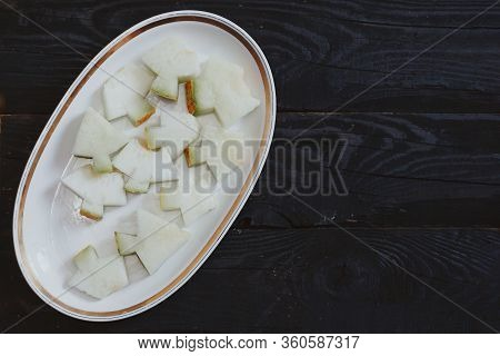 Slices Of Sweet Organic Summer Melons On The Dark Wooden Background. Sliced Ripe Melon On Wood. View