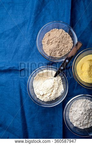 Various Vegetable Gluten Free Flour Corn,sesame,oat,coconut In Glass Bowl On Blue Textile Background