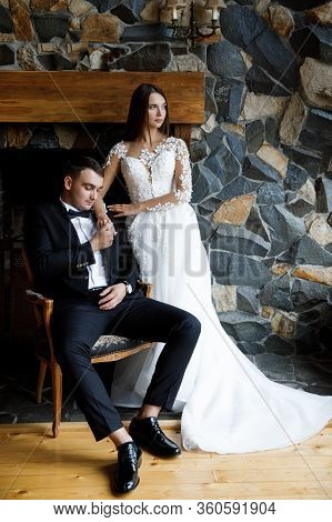 Stylish Bride And Groom Posing In Hotel Room. Happy Luxury Wedding Couple Embracing. Romantic Passio