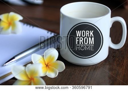 Coffee Cup With Text - Work From Home, With Bali Frangipani Flowers, Pen And Notebook On Desk. Socia