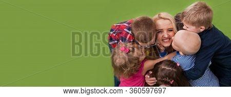 Group Of Children Boys And Girls Hug Teacher. Children Lovingly Hug Their Teacher In Kindergarten Or