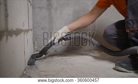 Worker Vacuuming Concrete Floors. Preparing The Floor For Waterproofing. Construction Cleaning With