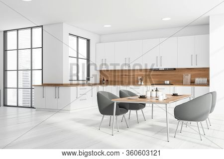 Corner Of Stylish Kitchen With White And Wooden Walls, Wooden Floor, White Countertops And Cupboards