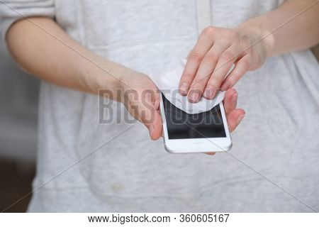 Person Cleaning Mobile Phone Screen With Disinfecting Wipes For Clean Smartphone. Covid-19 Coronavir