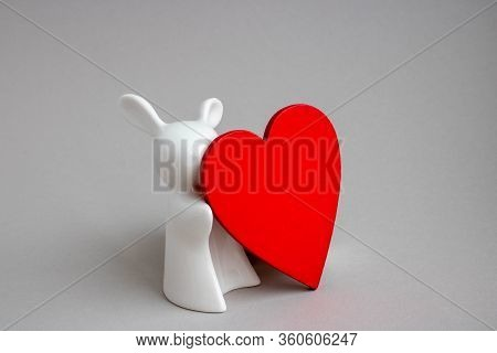 Beautiful Ceramic Rabbit On White Background. Statuette Of A White Rabbit With A Red Heart.easter De
