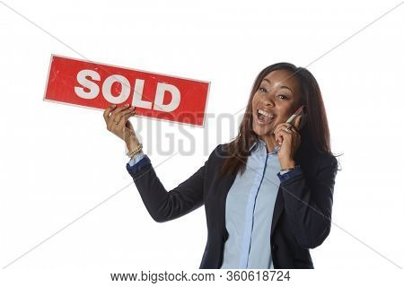 Young black woman holding a sold sign white talking on the phone isolated on a white background