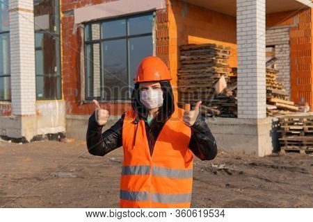 Female Construction Worker In Overalls And In Medical Mask Showing Thumbs Up On Background Of House