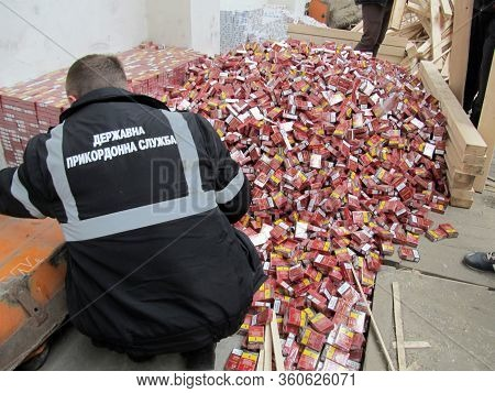 Krakovets, Ukraine - March, 2016: The Border Guarder Extracts Smuggled Cigarettes Disguised As Indus