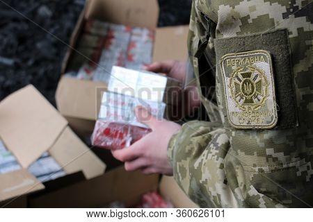 Shegini, Ukraine - Marh, 2017: The Border Guard In Camouflage Uniforms Puts Smuggled Cigarettes, Whi