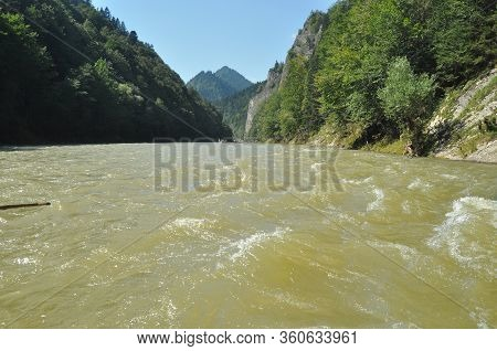 Rafting On The Dunajec River In The Pieniny National Park On Wooden Folding Shuttles Tied With A Rop
