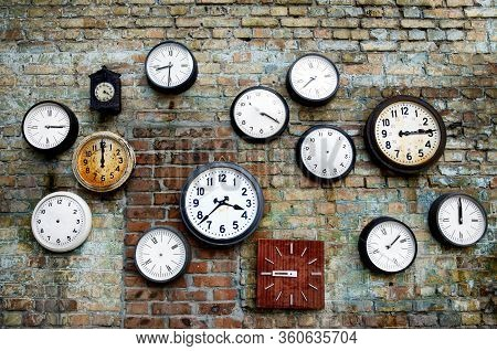 A Lot Of Vintage Clocks Of Different Sizes Hanging On A Grunge Brick Wall. Round And Square Clocks S