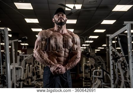 Muscular Male Physique Concept Of Strong Athlete Showing Big Muscles In Empty Gym