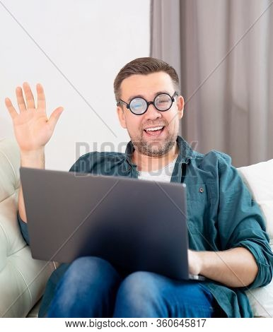 Male Freak With Glasses, Blogger, Freelancer, Businessman Working Online Lying On The Couch. Social