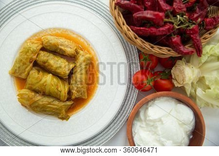 Meat Stuffed Cabbage Leaves, Stewed In Tomato Sauce . Cabbage Stuffing On A White Plate . Red Pepper