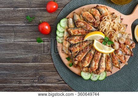 Fried Capelin, Sprats. Small Fried Fish On A Plate On A Wooden Background. Top View.