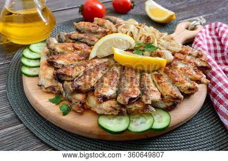 Fried Capelin, Sprats. Small Fried Fish On A Plate On A Wooden Background.