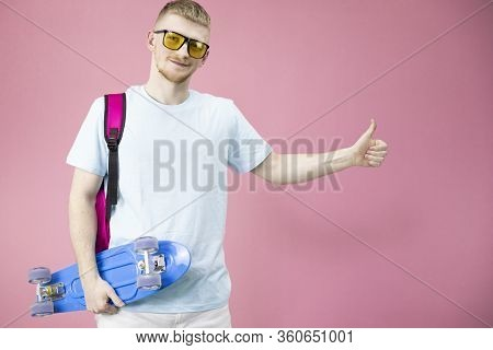 Handsome Caucasian Boy Or Teenager Student Holding Skateboard Pennyboard In Hands And Shows Thumb Up
