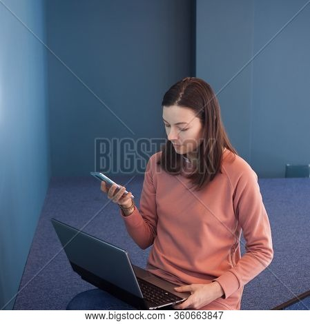 Young Woman In A Pink Jumper Works In A Coworking, Blue Background. Use Develop And Configure Cross-
