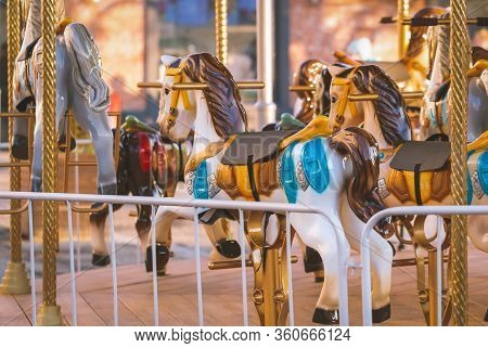 Colorful Children Carousel With Horses In An Amusement Park. Empty Old Fashioned Carousel.