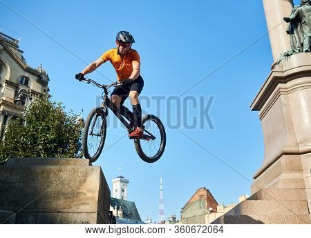Young Cyclist Performing Dangerous Jumps On Mountain Bike On Stairs Of Monument Pedestal Over Blue S