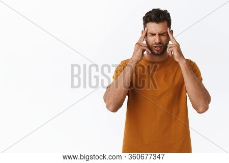 Upset And Distressed, Tensed Young Bearded Guy Suffering Terrible Migraine, Massaging Temples With I