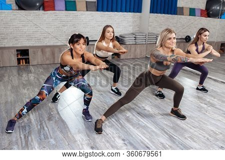 Group Of Four Young Sporty Girls Doing Weight Loss Workout In Fitness Class. Sport, Fitness And Life