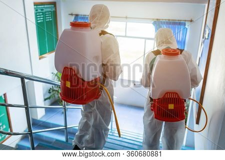 Disinfection, People In Virus Protective Ppe Suits And Mask Disinfecting Buildings Of Coronavirus Wi