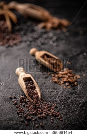 Gourmet Salts In Wooden Scoop On Black Background