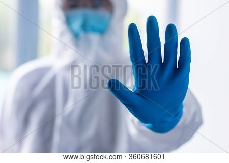 Doctor Wearing Ppe Suit, Mask And Face Shield For Protect Virus And Show Stop Hand Gesture For Socia