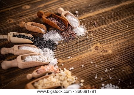 Crystals Of Kitchen Salt In Scoop On Wooden Background