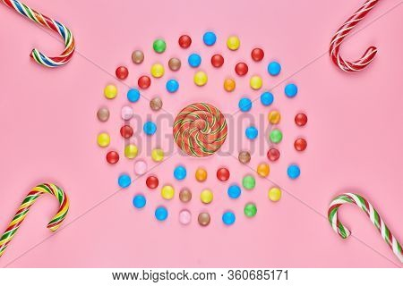 Sweet Lollipops And Candy Canes On Pink Background, Copy Space. Love To Colorful Sweetmeats In Child