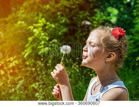 Young Girl In The Park Blowing On Dandelion