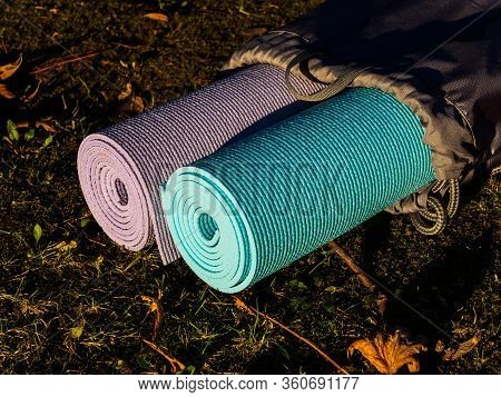 Yoga Mats In Grey Cover On Grass. The Concept Of A Healthy Lifestyle. Yoga Or Physical Education Cla
