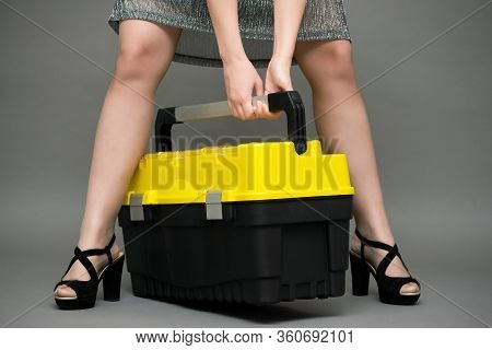 Female Legs In High Heel Shoes And Construction Tool Box On Gray Background. Woman Is Lifting A Heav