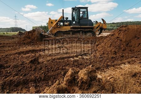 A Large Yellow Old Bulldozer At A Construction Site Prepares A Site For The Construction Of A Buildi