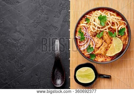 Khao Soi Gai Or Thai Coconut Curry Noodle Soup In Black Bowl At Dark Slate Background. Khao Soy Is T