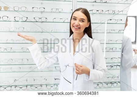 Female Ophthalmologist. Happy Seller Showing Eyeglasses Assortment On The Display Shelf Showcase In