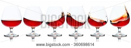 Set Of Brandy Snifters With Cognac Splashes. Splashes Of Cognac In Glasses, Isolated On White Backgr