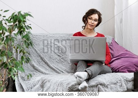 Young Girl Stay Home In Quarantine, Relaxing On The Couch And Using The Computer. Woman Lies On Sofa