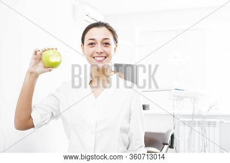 Photo Of A Young Woman Dentist Doctor With A Green Apple. Woman Dentist Smiling In The Office. Beaut