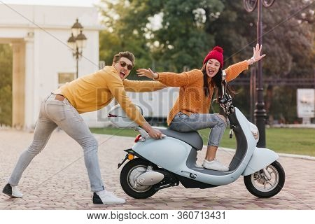 Inspired Girl In Trendy Red Hat Spending Time With Boyfriend And Driving Scooter With Smile. Outdoor