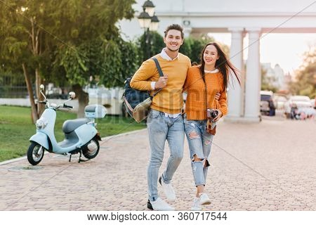 Full-length Portrait Of Laughing Couple In The Same Outfit Walking In Park Together. Wonderful Dark-