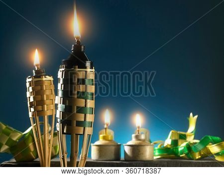 bamboo torch  oil lamp and ribbon ketupat on the blue background